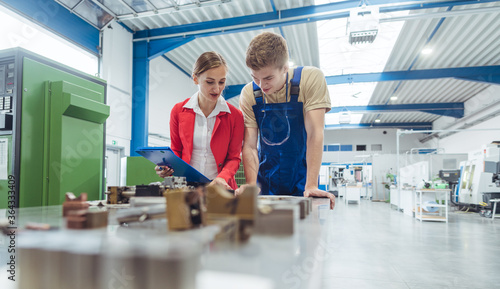 Fotografiet Manufacturing worker and manager during quality inspection