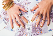 Hands Of Rich Woman With Golde...