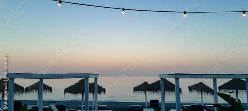Photo Restaurante en la playa con sombrillas y hamacas vacías al atardecer, con bombillas encendidas colgadas