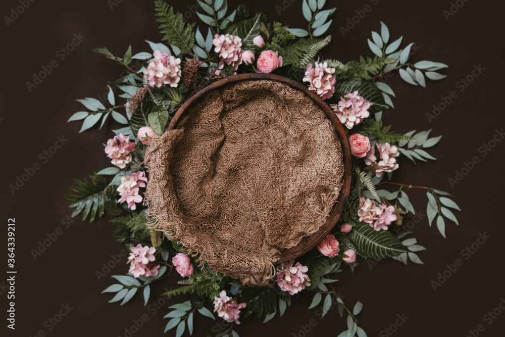 Fototapeta Newborn digital background - brown wooden bowl with green leaves wreath and jute layer.