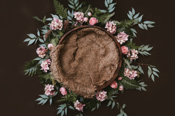 Newborn digital background - brown wooden bowl with green leaves wreath and jute layer.