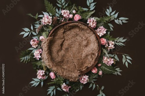 Obraz na płótnie Newborn digital background - brown wooden bowl with green leaves wreath and jute layer
