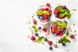 Fototapeta Kawa jest smaczna - Parfait with granola, jam and fresh berries in the glass jar.