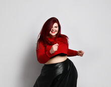 Overweight Redhead Woman In Red Spiked Top, Black Bra And Leather Skirt. Dancing And Smiling, Posing Isolated On White Background