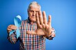 Senior handsome hoary man holding blue cancer ribbon symbol over isolated background with open hand doing stop sign with serious and confident expression, defense gesture