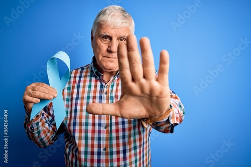 Fototapeta Senior handsome hoary man holding blue cancer ribbon symbol over isolated background with open hand doing stop sign with serious and confident expression, defense gesture obraz