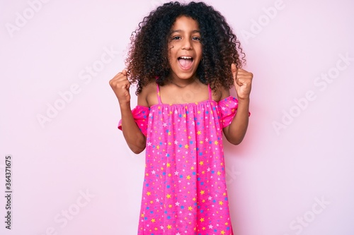 African american child with curly hair wearing casual dress celebrating surprised and amazed for success with arms raised and open eyes. winner concept.