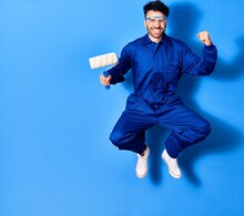 Young Handsome Hispanic Man Wearing Painter Uniform And Cap Smiling Happy. Jumping With Smile On Face Over Isolated Blue Background