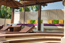 This Unique Photo Shows A Pool Area With Sun Beds And Umbrellas And A Seat With Decorative Colorful Cushions. The Picture Was Taken In Thailand
