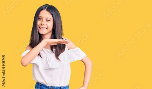 Valokuvatapetti Beautiful child girl wearing casual clothes gesturing with hands showing big and large size sign, measure symbol
