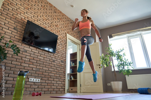 Fotografie, Obraz Fit sporty active young adult woman wearing sportswear doing fitness sport exercise at home