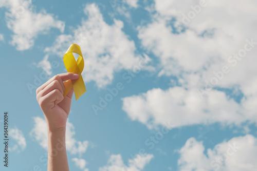 Tela Hands holding yellow gold ribbon over blue sky, Sarcoma Awareness, Bone cancer,