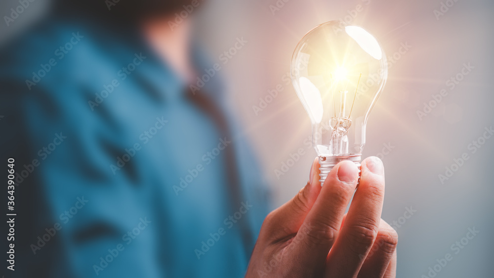 Fototapeta Idea innovation and inspiration concept.Hand of man holding illuminated light bulb, concept creativity with bulbs that shine glitter.Inspiration of ideas for sustainable business development.