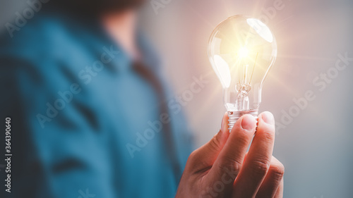 Idea innovation and inspiration concept.Hand of man holding illuminated light bulb, concept creativity with bulbs that shine glitter.Inspiration of ideas for sustainable business development.