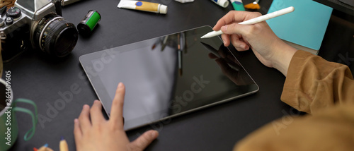 Photo Female designer drawing on digital tablet with stylus pen on worktable with pain