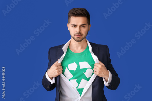 Fototapeta Man wearing t-shirt with recycling sign on color background. Ecology concept obraz