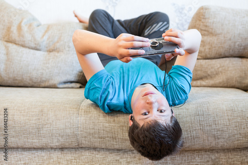 Photo Attractive youngster guy wearing blue t-shirt lying on his back on couch and hol