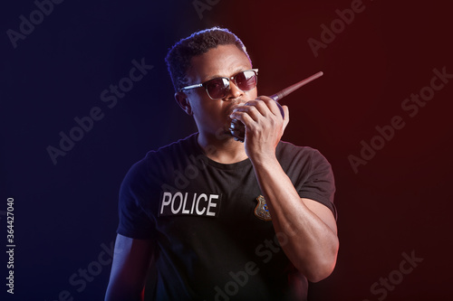 Fotografie, Obraz African-American police officer with two-way radio on dark background