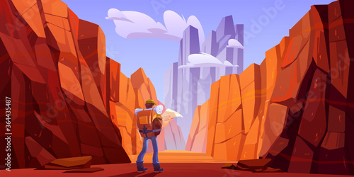 Canvas Print Hiker man with map on desert road in canyon with red mountains