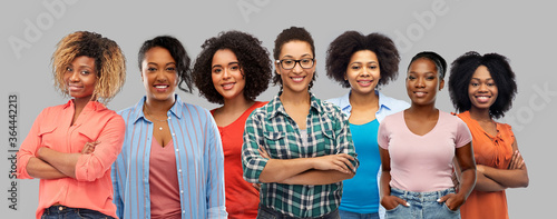 Obraz civil rights, ethnicity and people concept - group of happy african american women over grey background - fototapety do salonu