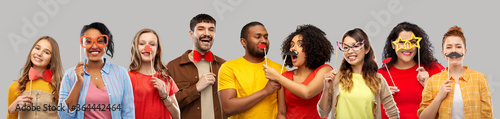 Платно photo booth and fun concept - happy smiling people with party props over grey ba
