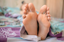 Women's Feet With Long Fingers Protrude From Under The Blanket. Concept Of Sleep And Rest