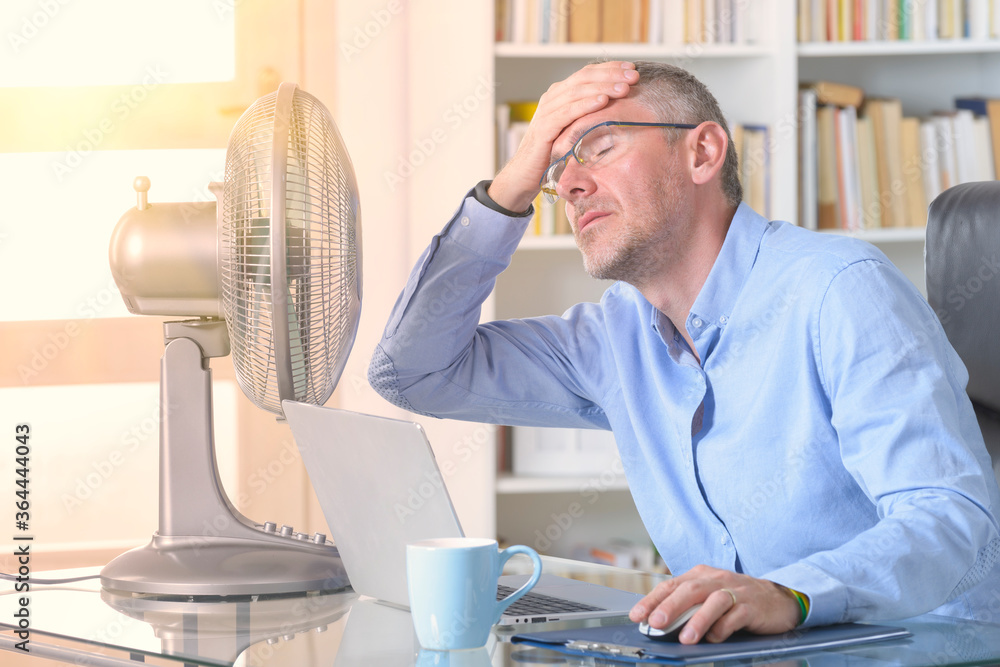 Fototapeta Man suffers from heat in the office or at home