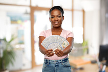 Finance, Currency And People Concept - Happy African American Young Woman Holding Hundreds Of Dollar Money Banknotes Over Office Background