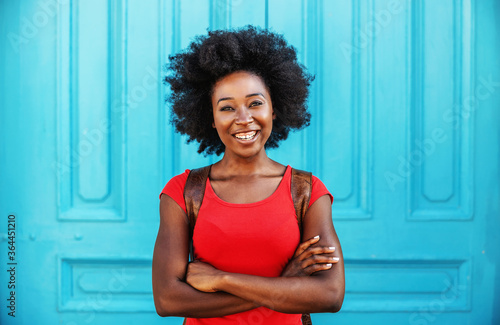 Photo Young gorgeous smiling african woman standing outdoors with arms crossed