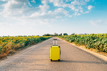 Yellow Suitcase On A Road With...