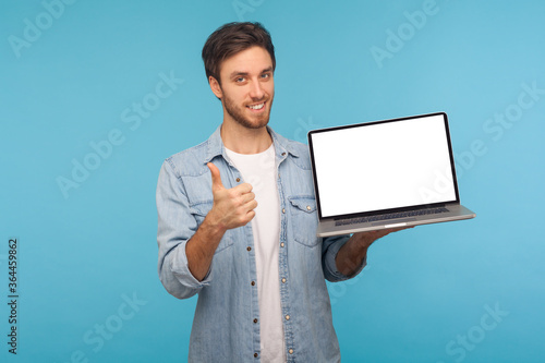 Fotografia Portrait of satisfied smiling handsome man in worker denim shirt showing thumbs up and holding laptop screen with empty display, mock up for commercial image