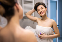 Young Asian Woman Washing Her Face With Water In The Bathroom While Looking Herself In The Mirror