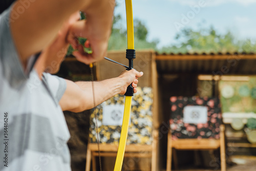 Archer holds yellow bow aiming at a target, during a open air corporate team building Canvas Print