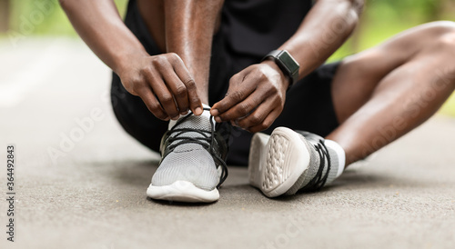 Closeup of black sportsman tying his shoelaces before training Canvas