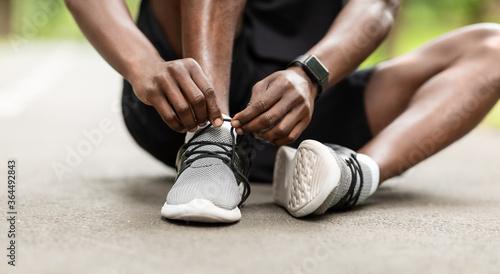 Fotografiet Closeup of black sportsman tying his shoelaces before training