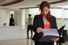 Hispanic Businesswoman Reading...