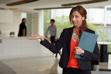 Happy Hispanic Businesswoman Showing Something In The Office Building