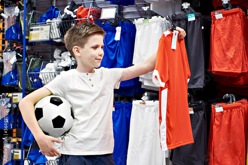 Fototapeta Boy with ball and red t-shirt in football store obraz