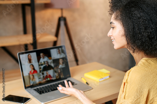 Tablou Canvas Young woman uses app on laptop for video communication with a diverse multiracial group of coworkers