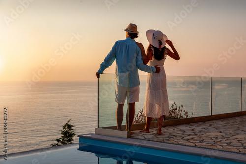 Cuadros en Lienzo Romantisches Paar im Sommerurlaub steht am Pool und genießt den Sonnenuntergang