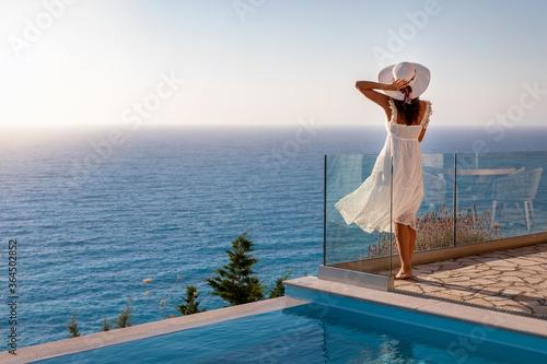 Eine Frau in weißem Sommerkleid im Urlaub steht am Pool und schaut auf das medit Wallpaper Mural