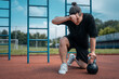 exhausted man athlete taking break between exercising with kettlebell outdoor