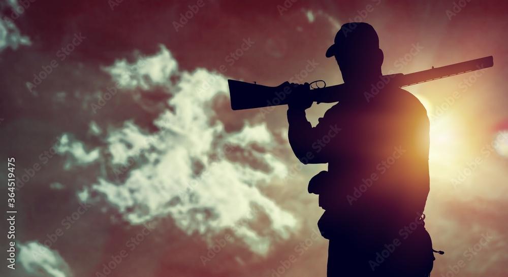 Fototapeta Male hunter silhouette with a gun at sunset