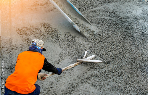 Fototapeta Pouring ready-mixed concrete after placing steel reinforcement to make the road