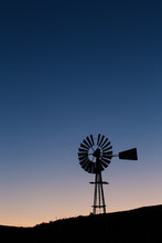Windpomp/Windmill Silhouette Against The Fast Approaching Dawn Over The Tankwa Karoo In South Africa
