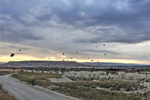 The Unique Landscape Of Cappadocia At Dawn. The Road Passes Near The Gorge. There Are Dark Clouds In The Sky. Far Above The Flat-top Mountain, The Sun Rises. Many Colorful Balloons Rise Into The Air.