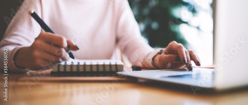 Fototapeta Selective focus on hipster girl writing interesting ideas for scenario for school performance while making research on content websites, woman typing text message via laptop keyboard for send reply obraz