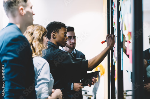 Fototapety, obrazy: Pensive diverse group of young people dressed in formal wear writing notes on colorful stickers glued on wall during collaborative process in office.Multicultural students cooperating on common task