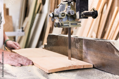 Male woodworker in casual clothes focusing and cutting lumber using special electric machine while working in light modern workshop - 364554438