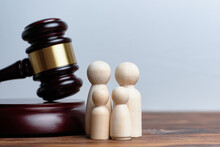 The Concept Of Adopting Children By A Family. The Hammer Of A Judge With Abstract Figures Of People.